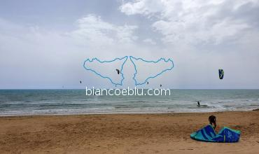 a windy day and people play kite surf in marina di ragusa